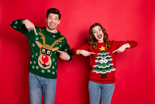 Man and woman wearing Christmas jumpers